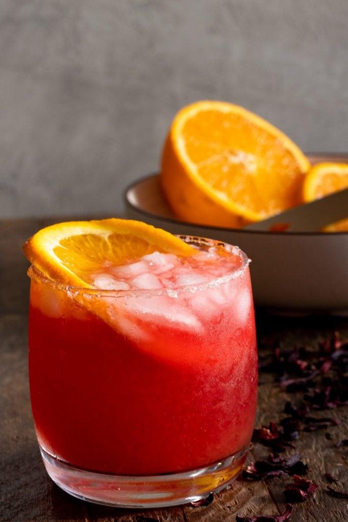 Salt rimmed orange hibiscus margarita in clear drinking glass