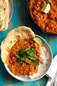 bowl of butter chicken over rice on blue background