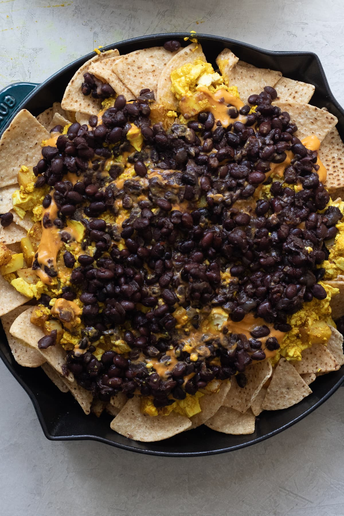 Nacho cheese, potatoes, tofu scramble and black beans layered on top of chips in large skillet.