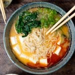large ramen bowl topped with spinach, tofu, green onion, sesame seeds and chili oil on wooden background