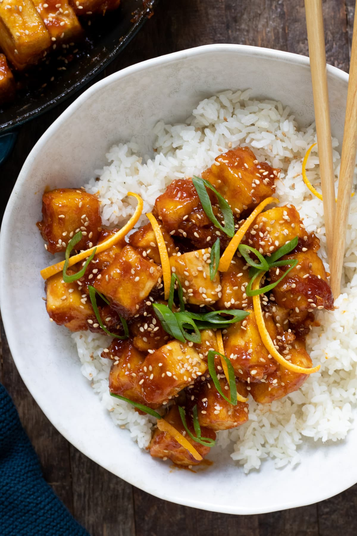 Orange chicken sprinkled with sesame seeds in large white bowl over white rice