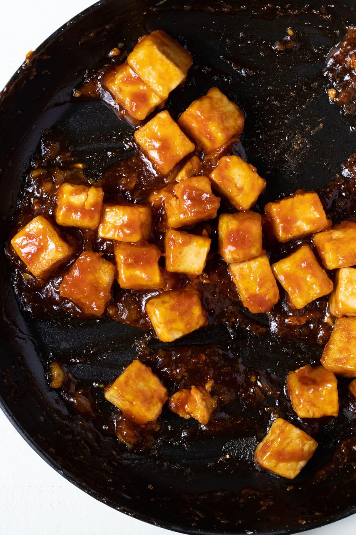 Tofu cubes in orange sauce glaze in cast iron skillet