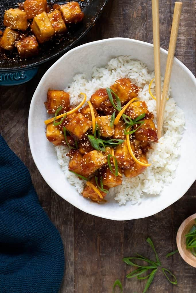 orange tofu chicken over white rice with chopsticks on wood table