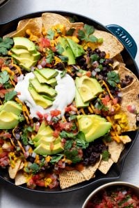 vegan chilaquiles layered in a large cast iron skillet