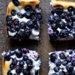 Cheesecake bars topped with fresh blueberries and pinterest text.
