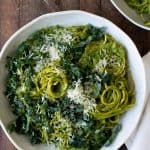 white bowl filled with creamy pesto pasta swirls, topped with kale and parmesan cheese on wooden table