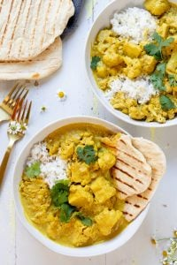 two bowls of yellow curry with naan bread over rice in white bowl