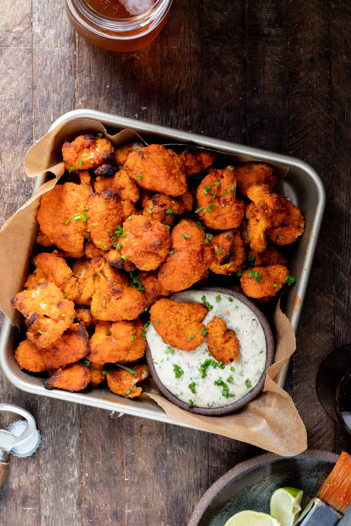 baked cauliflower buffalo wings in square container with a glass of cold beer and limes