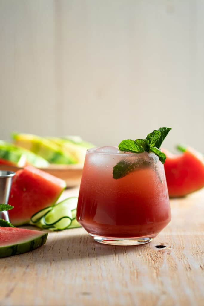 cocktail on light wood board with watermelon slices and cucumber ribbons beside it