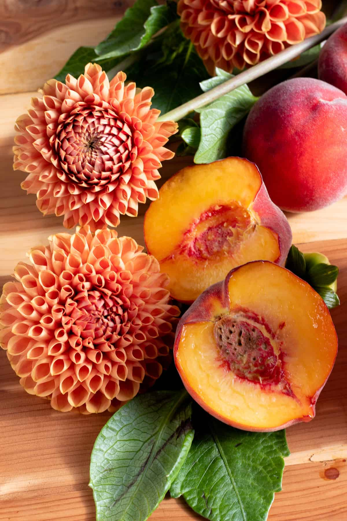 peaches cut in half and flowers on wooden table