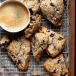 vegan blueberry lemon poppy seed scones on cooling rack with a cup of coffee