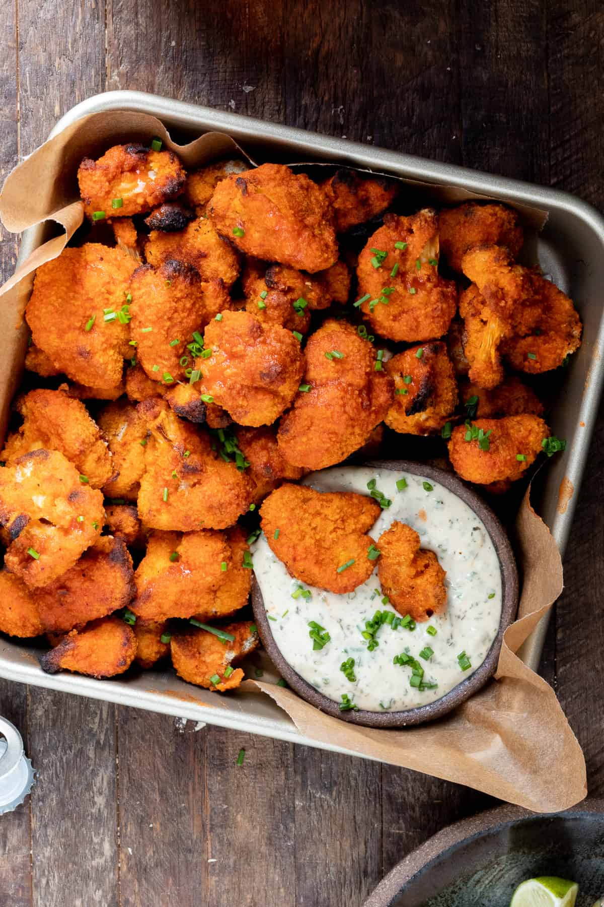 vegan buffalo wings in square dish with parchment paper dipped in ranch dressing