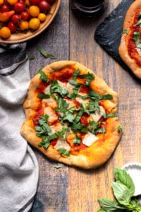 vegan flatbread margherita pizza on wood background with a glass of wine and fresh tomatoes