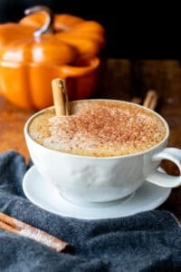 latte in white mug with pumpkin pie spice on wooden table