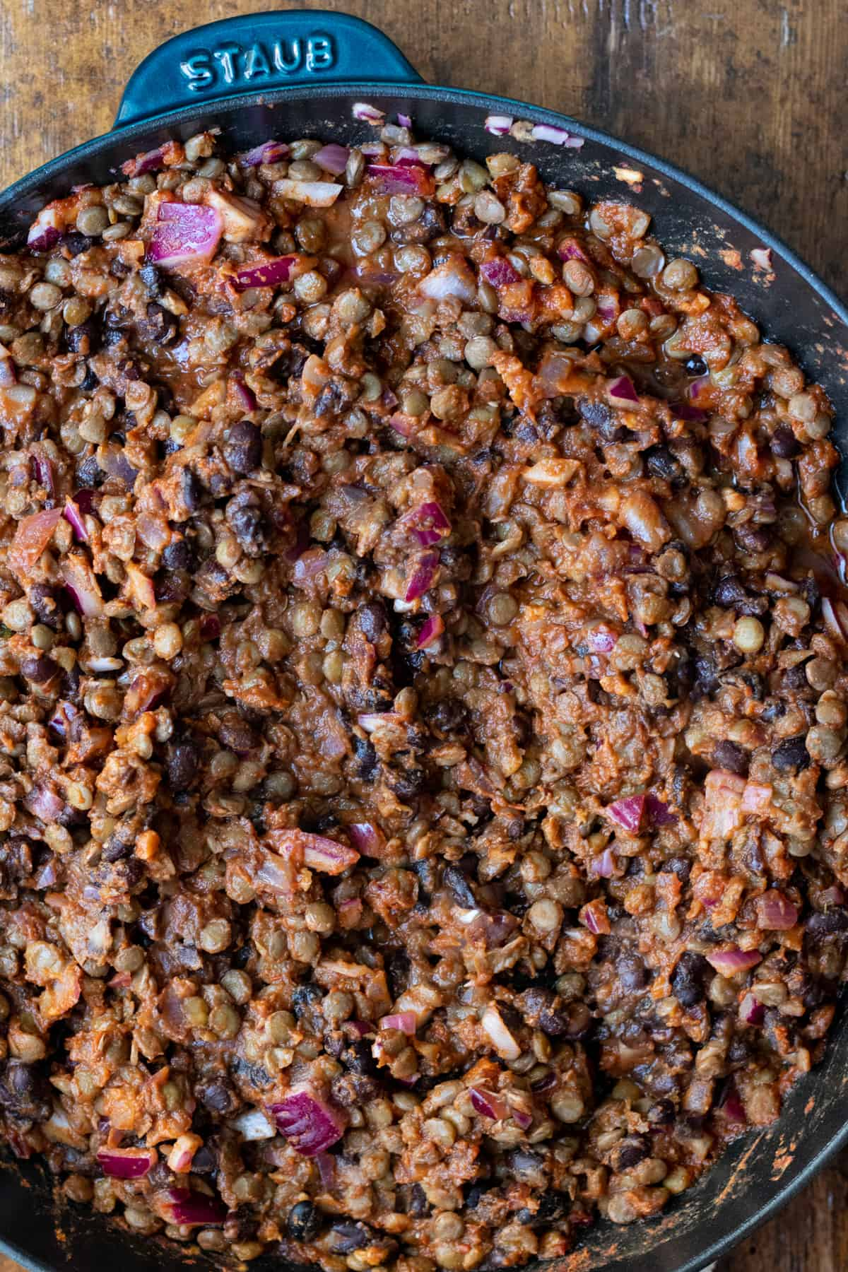 lentil and black bean mixture in cast iron skillet tossed in adobo sauce