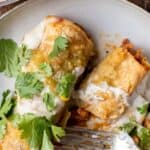 Two cheesy enchiladas on plate with 1 cut in half by fork.