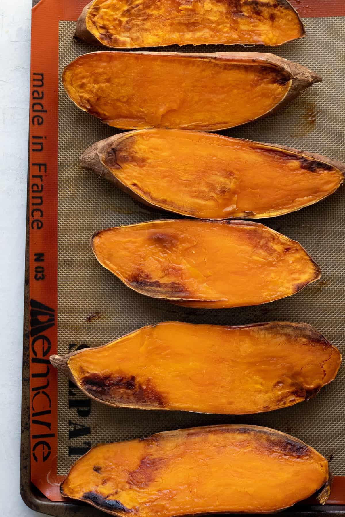 halved sweet potatoes on baking sheet after roasting