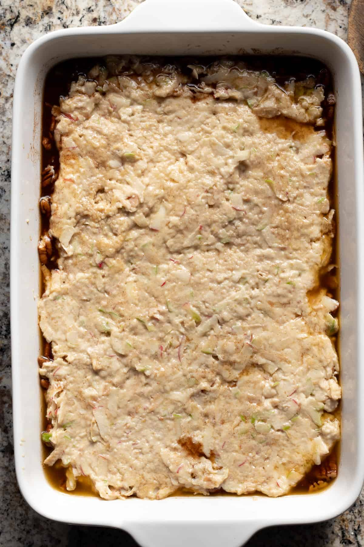 cake batter overtop sticky maple glaze in casserole dish