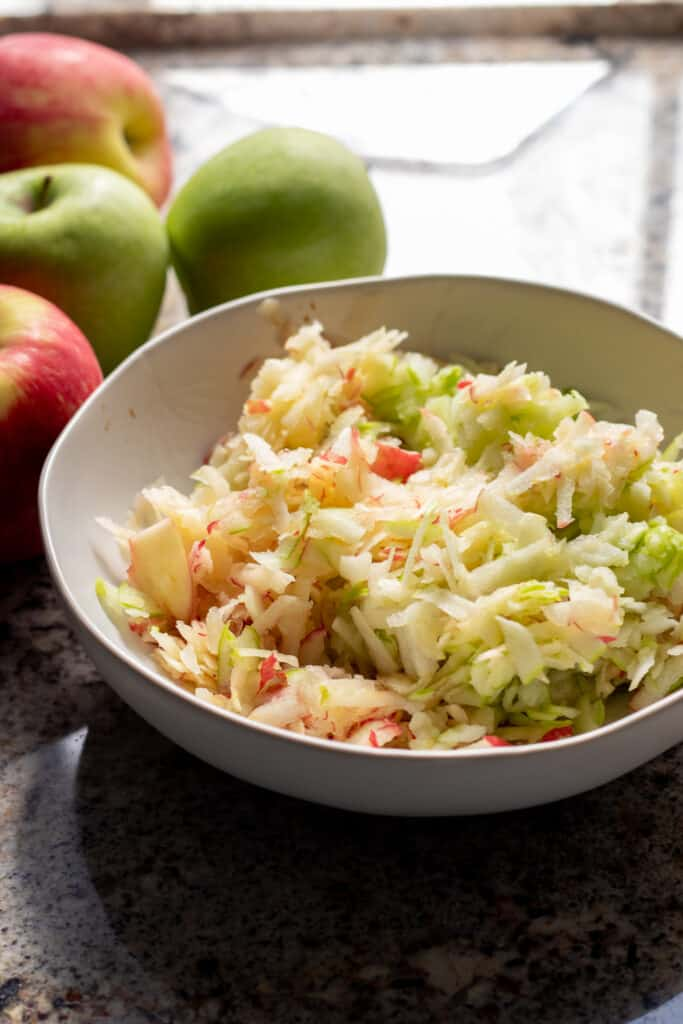 Grated apples in white bowl