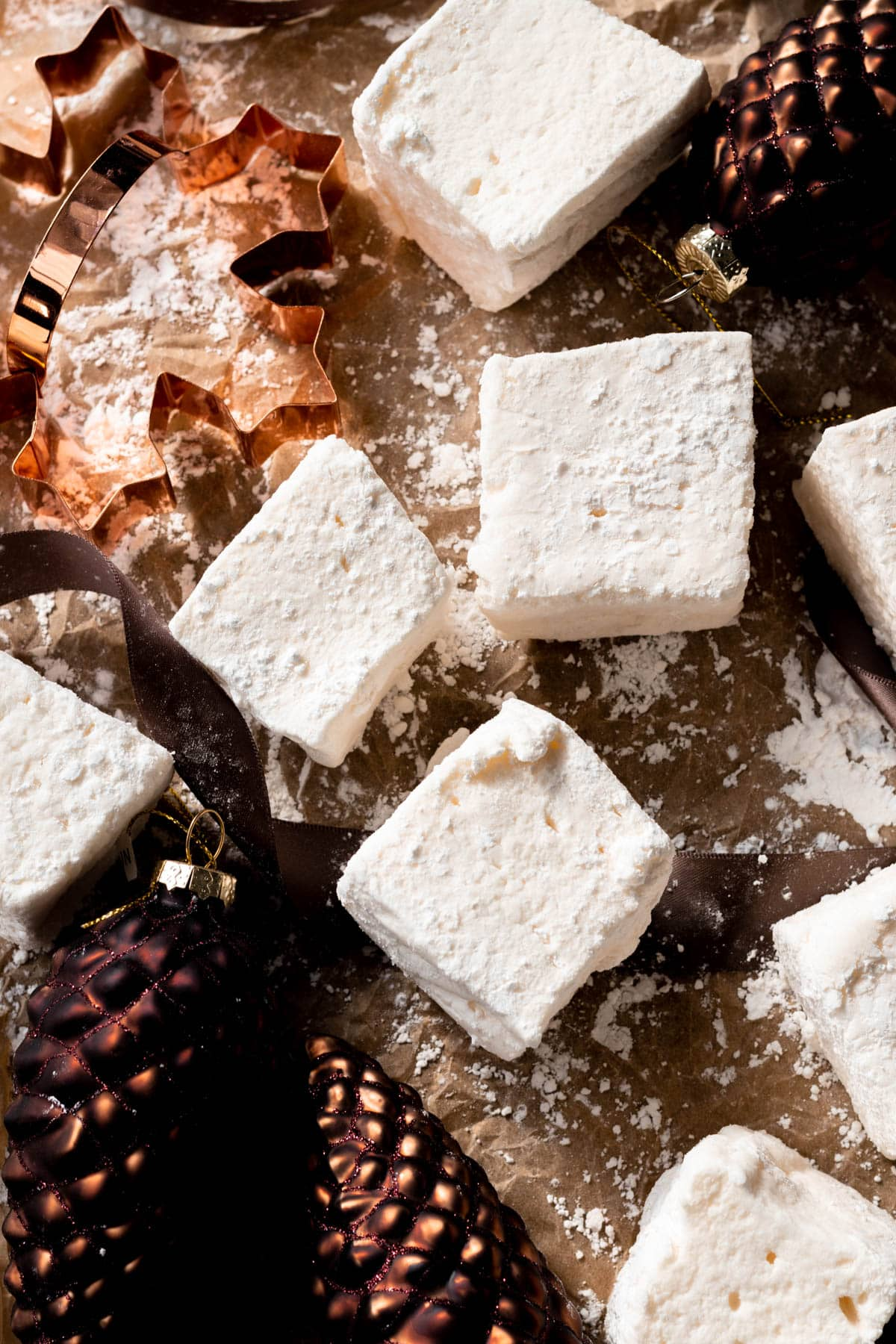 Marshmallows on parchment paper surrounded by ornaments.