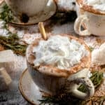 Three mugs with saucers of hot chocolate topped with coconut whipped cream and garnished with rosemary.