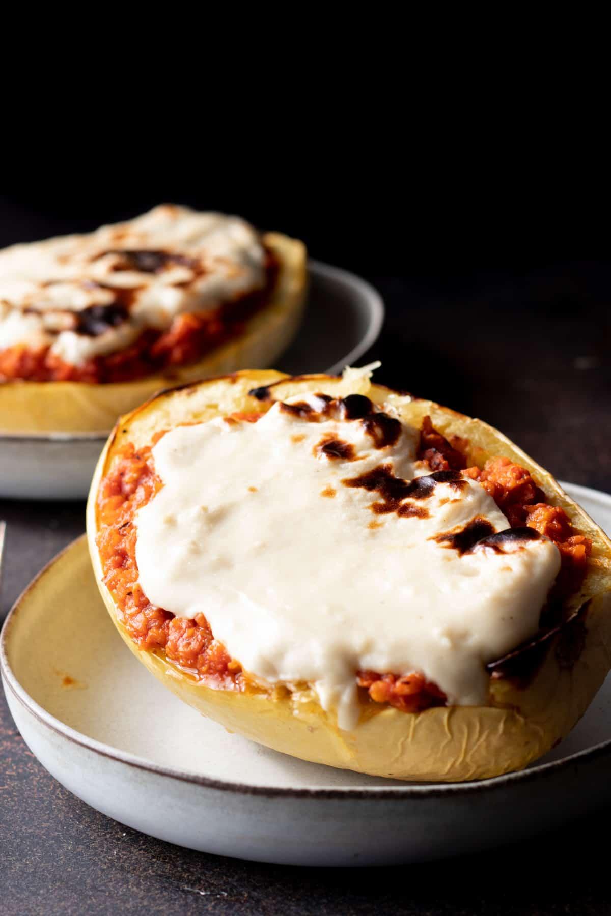 Vegan mozzarella melted on top of spaghetti squash lasagna boat.
