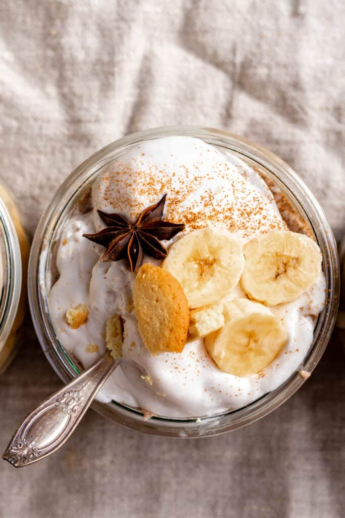 Sliced banana and star anise on top of pudding with spoon in jar.