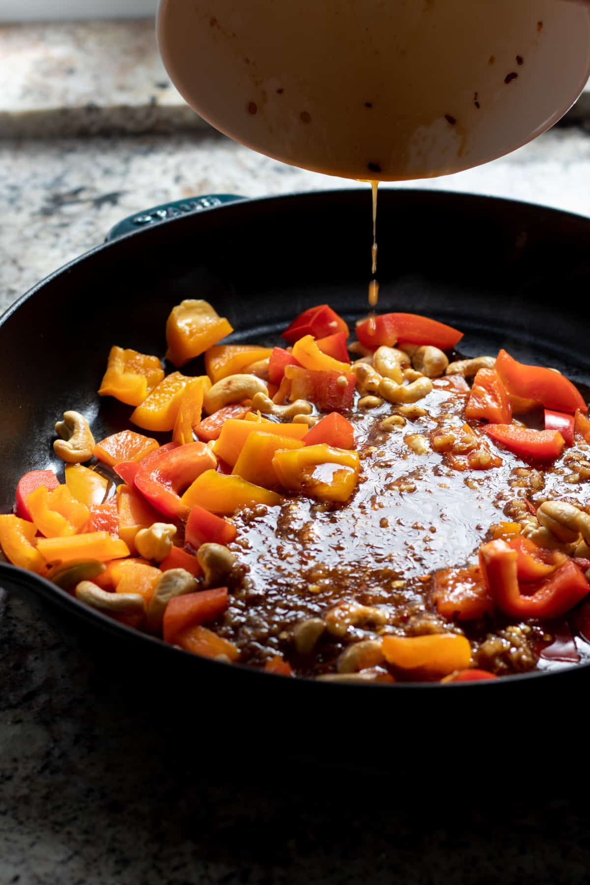 Adding the sauce to the cashews and bell pepper in the skillet.