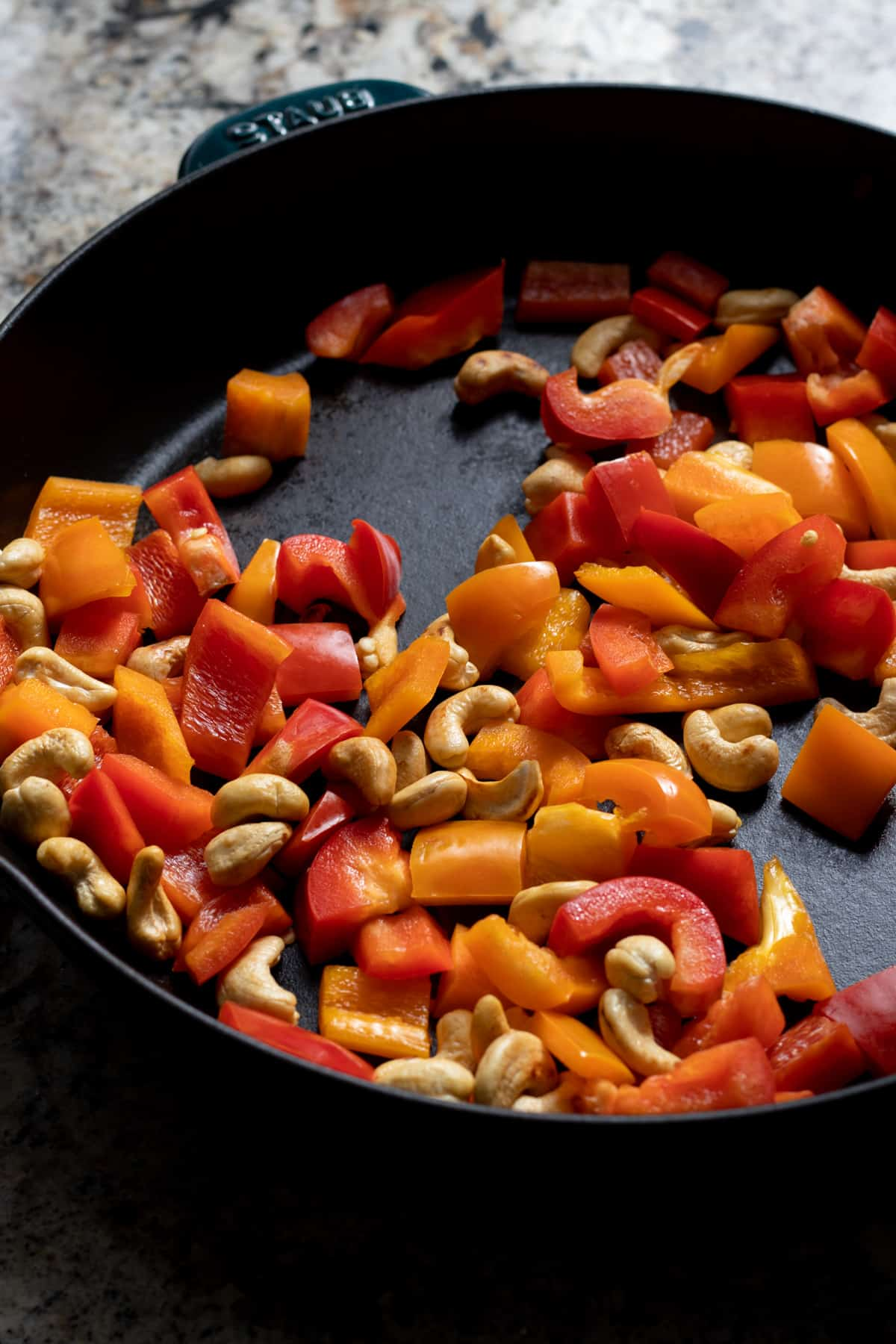 Cashews and bell pepper dry roasted in a cast iron skillet.