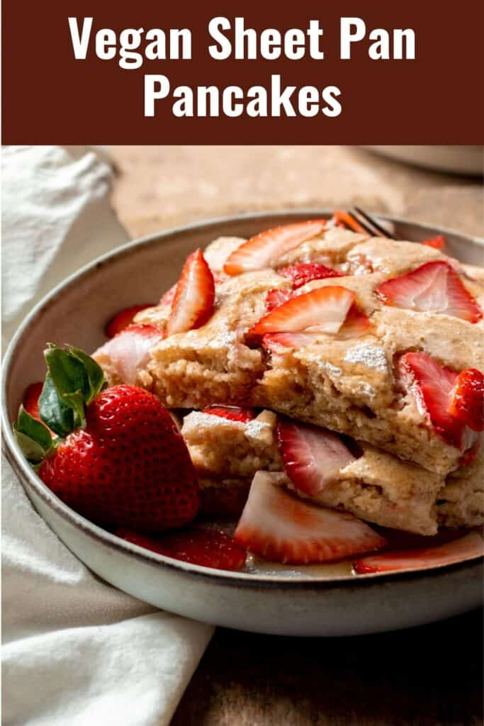 Stack of pancakes topped with strawberries in shallow bowl.