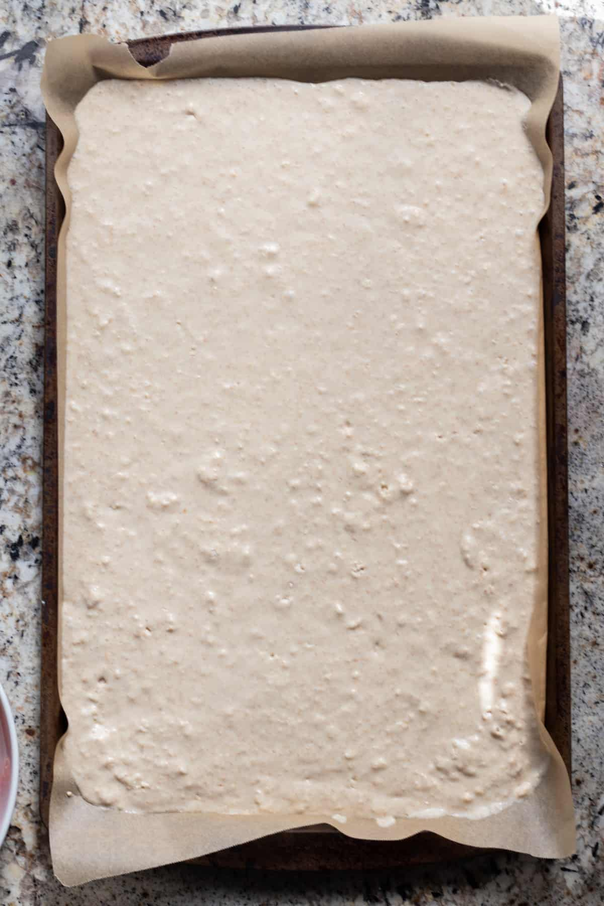Pancake batter in parchment lined baking sheet.