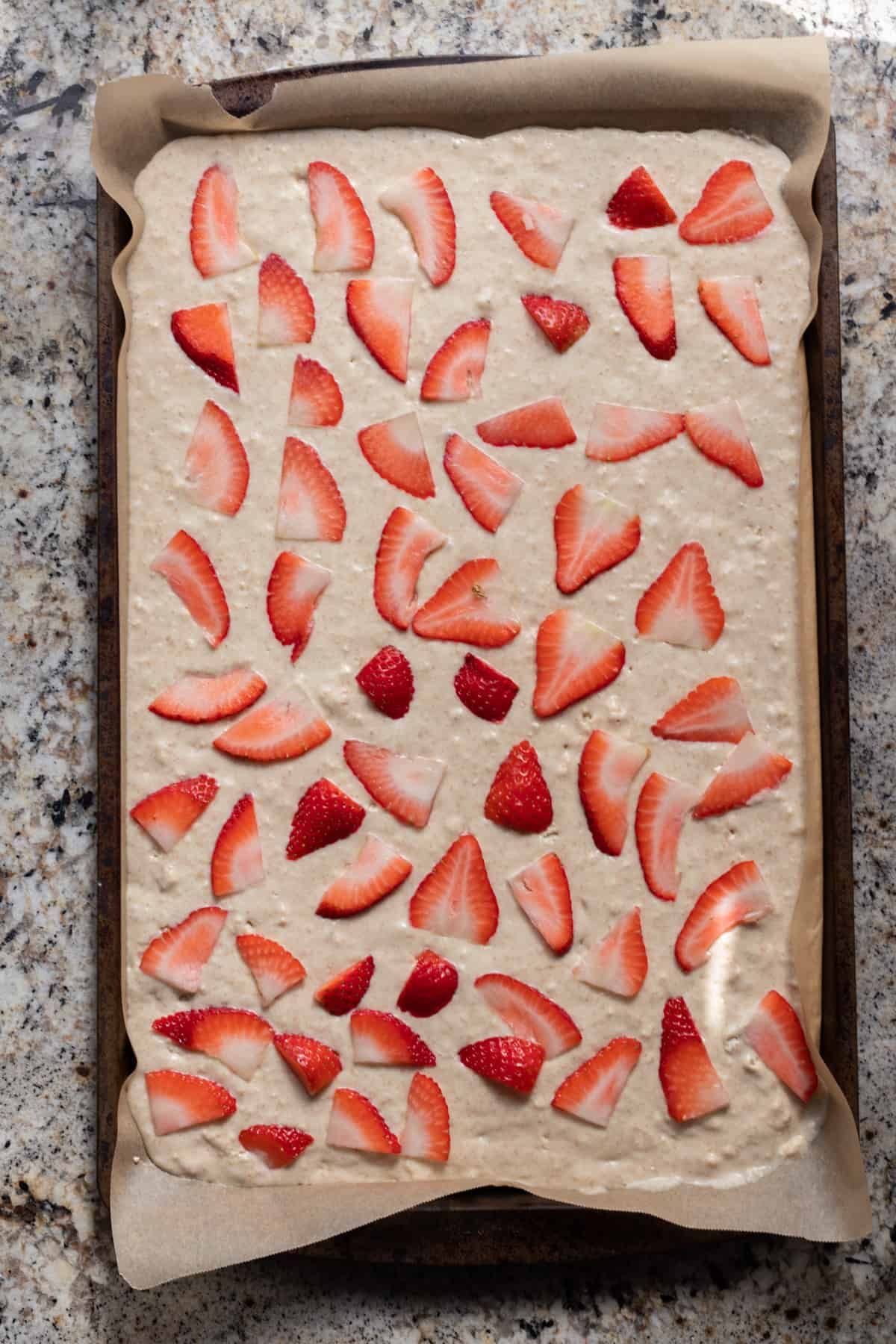 Pancake batter spread in sheet pan topped with sliced strawberries.