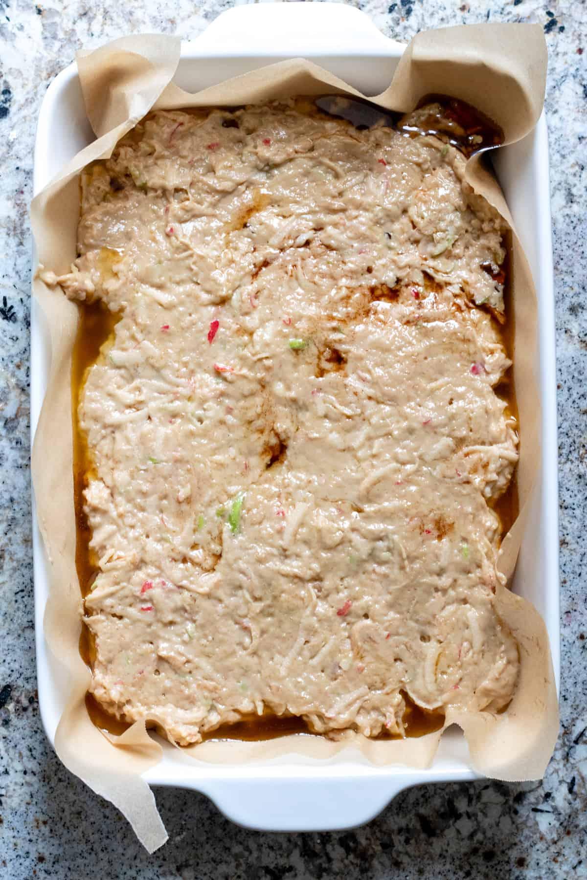 Apple cake spread over glaze in baking dish!