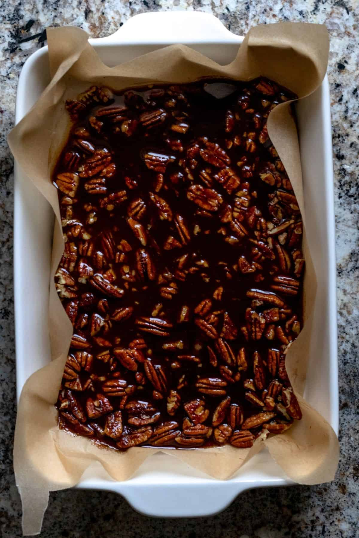 Glaze poured over chopped pecans in casserole dish.