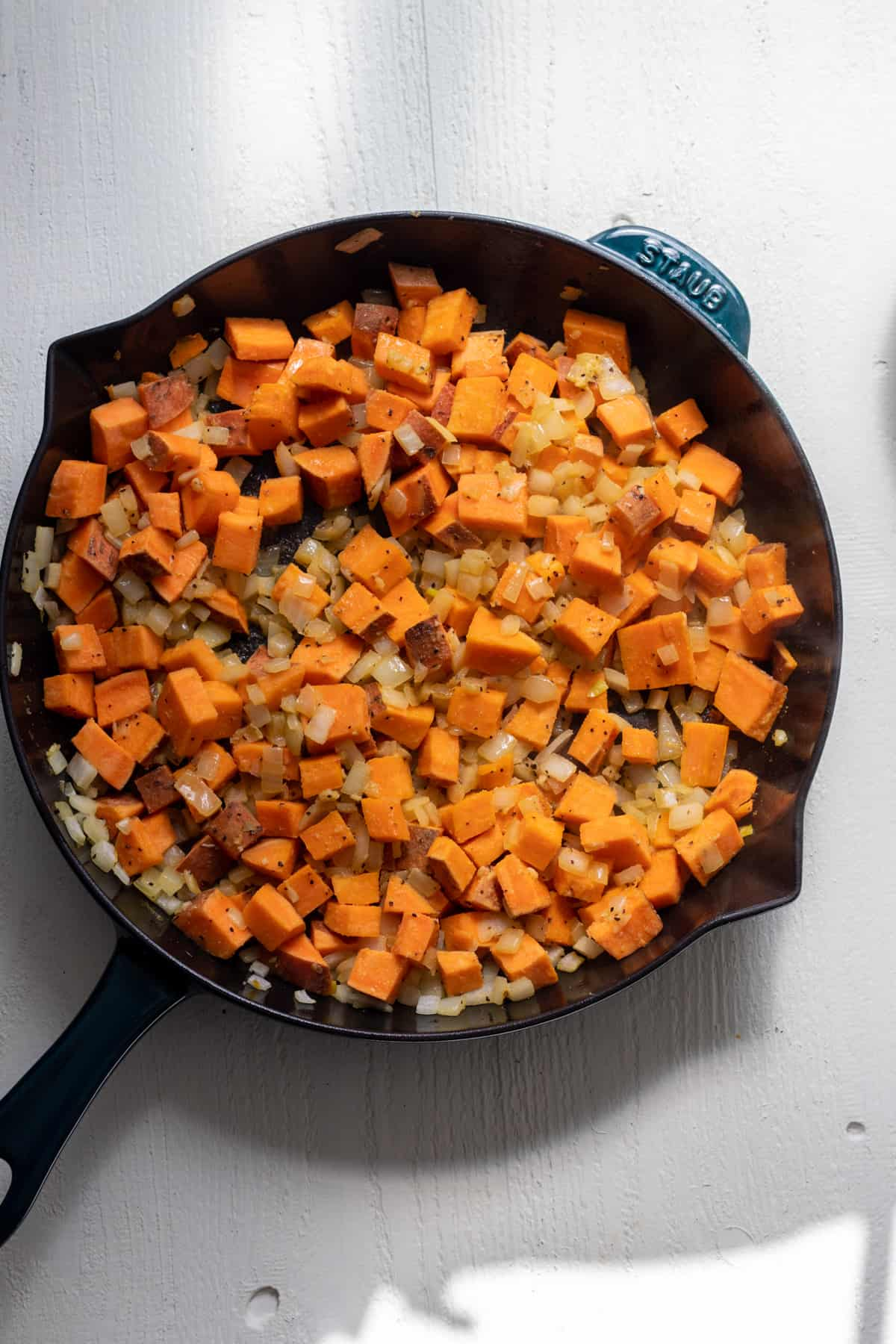 Sweet potato sauteed with onion in skillet.
