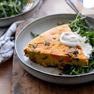 Frittata on plate with arugula and dollop of vegan sour cream.