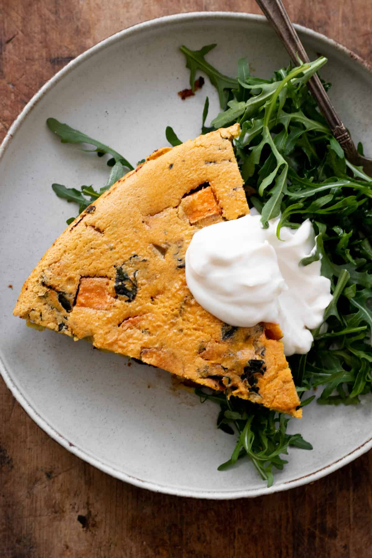 Frittata slice over arugula on gray plate.