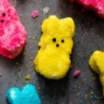 Yellow, pink, and blue peep marshmallows on dark surface.