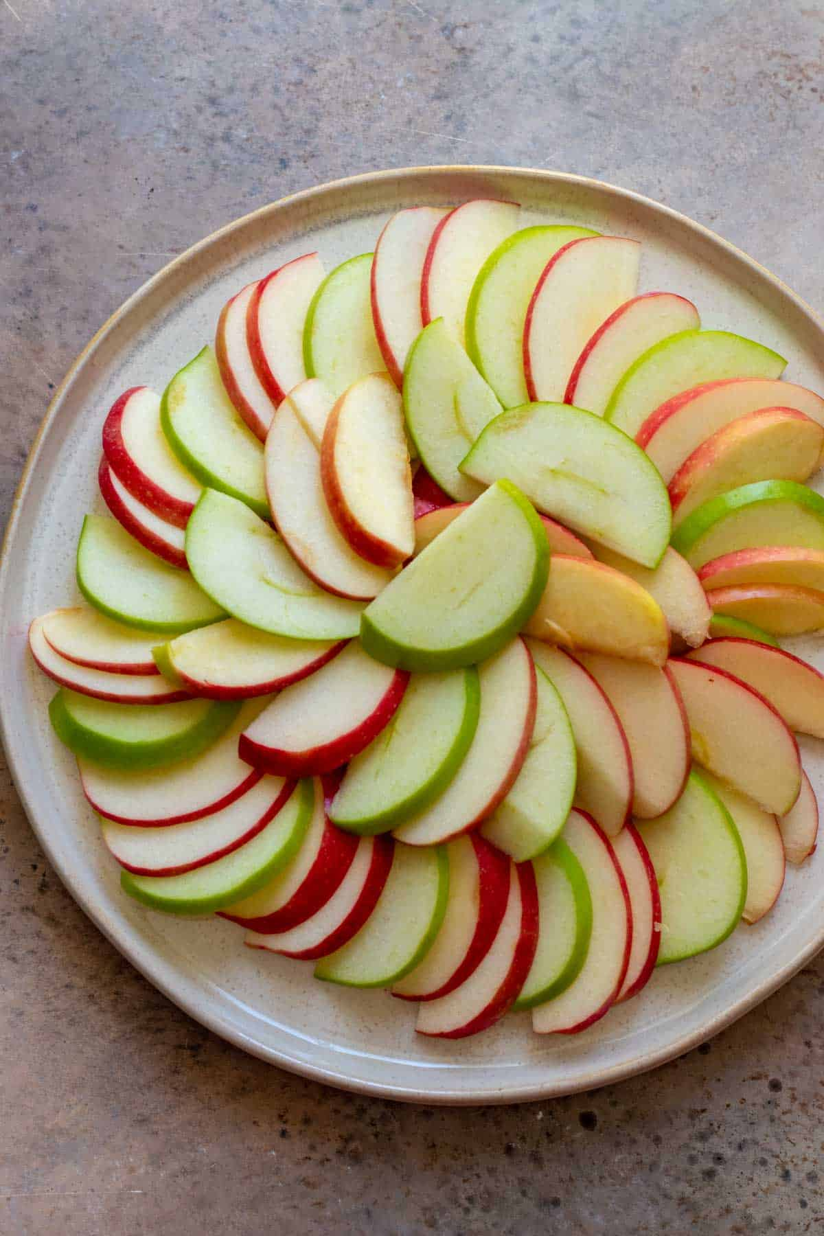 Thinly sliced apples layered on large plate in circular pattern.