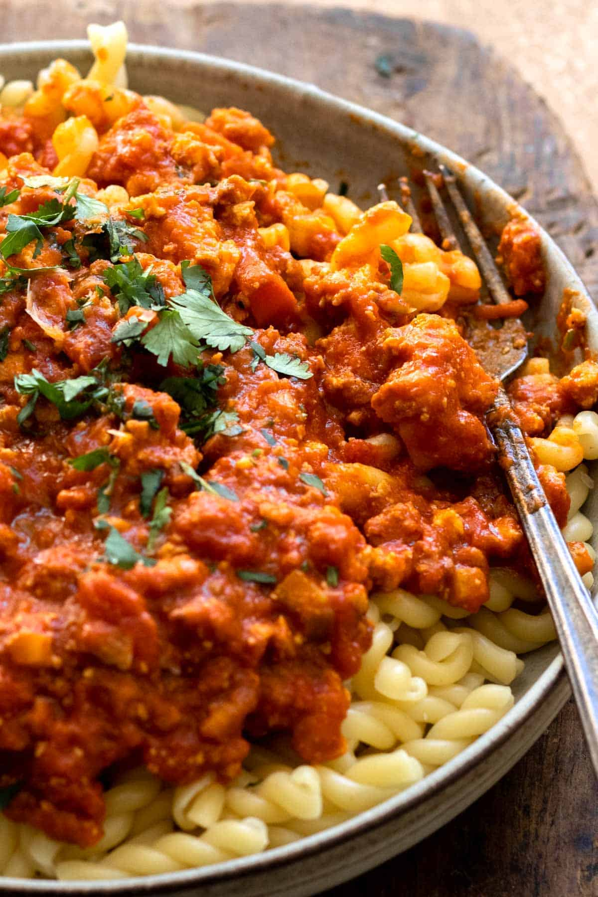 Finished bolognese dish sprinkled with fresh parsley over pasta.