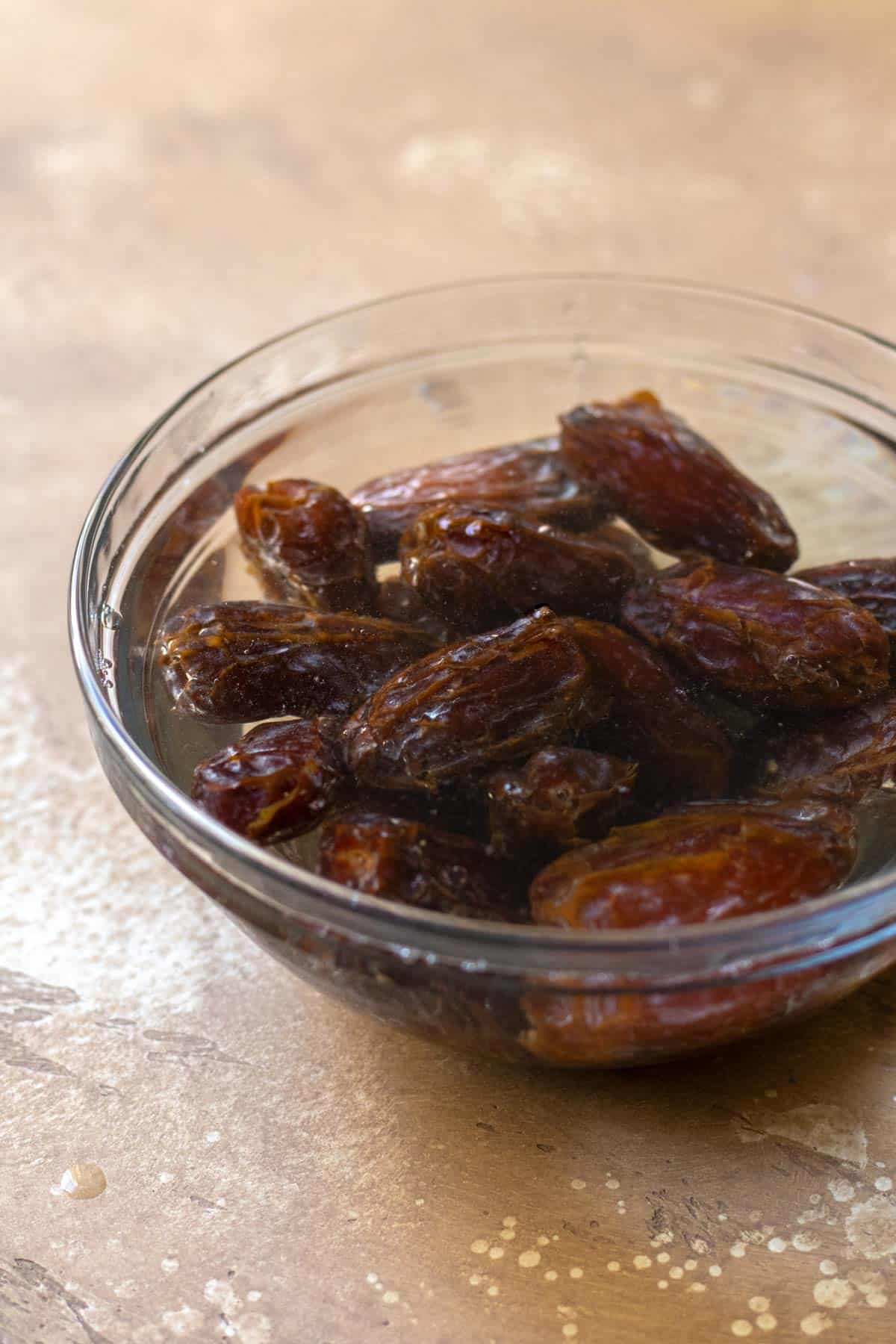 Medjool dates soaking in hot water in glass bowl.