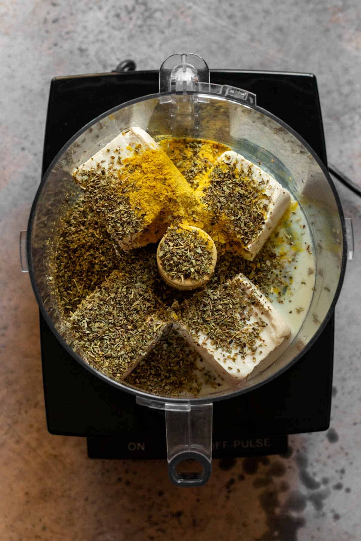 Spices added in overtop tofu in food processor.