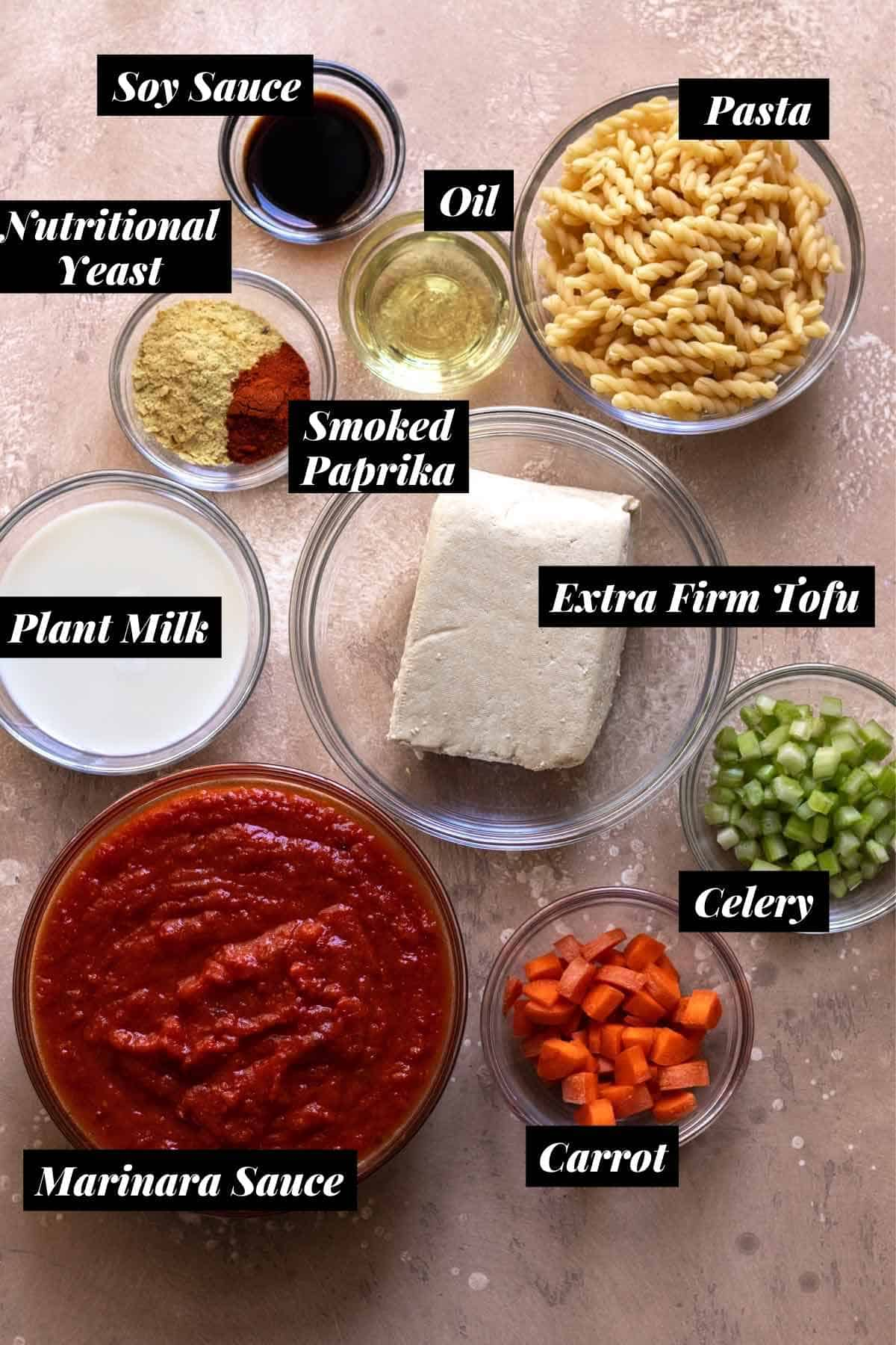 Bolognese ingredients measured into individual glass bowls and labeled.