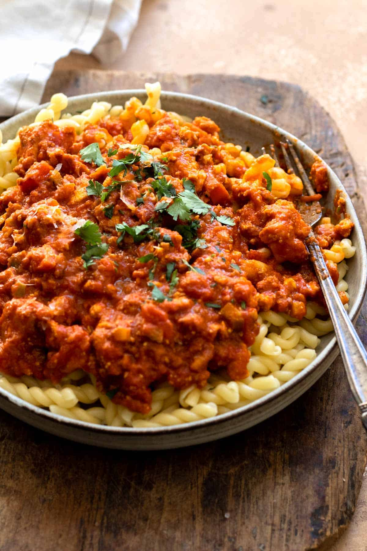 Bolognese served over pasta in a gray shallow bowl.