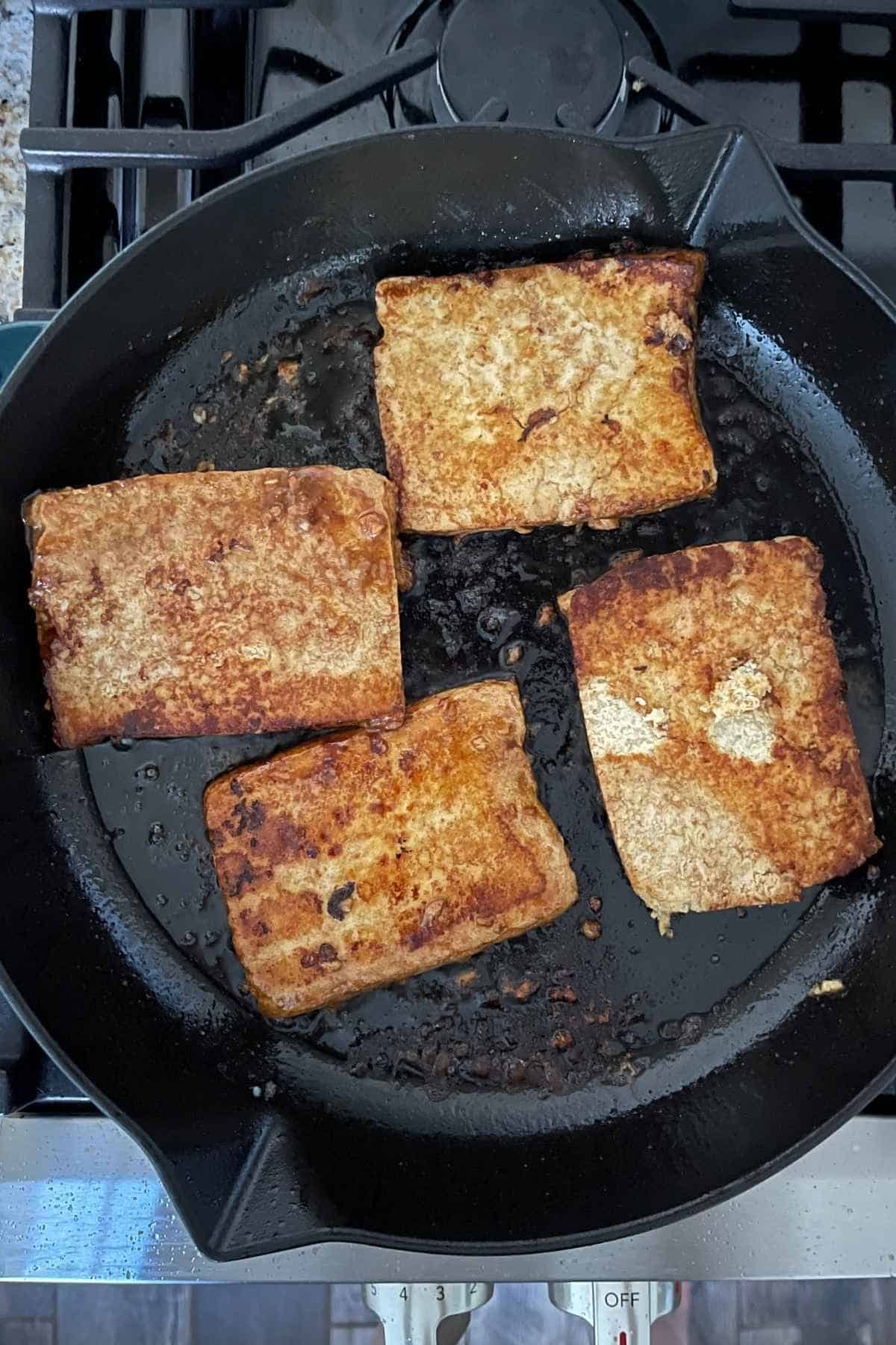 Tofu slices pan frying in large cast iron skillet on stove.