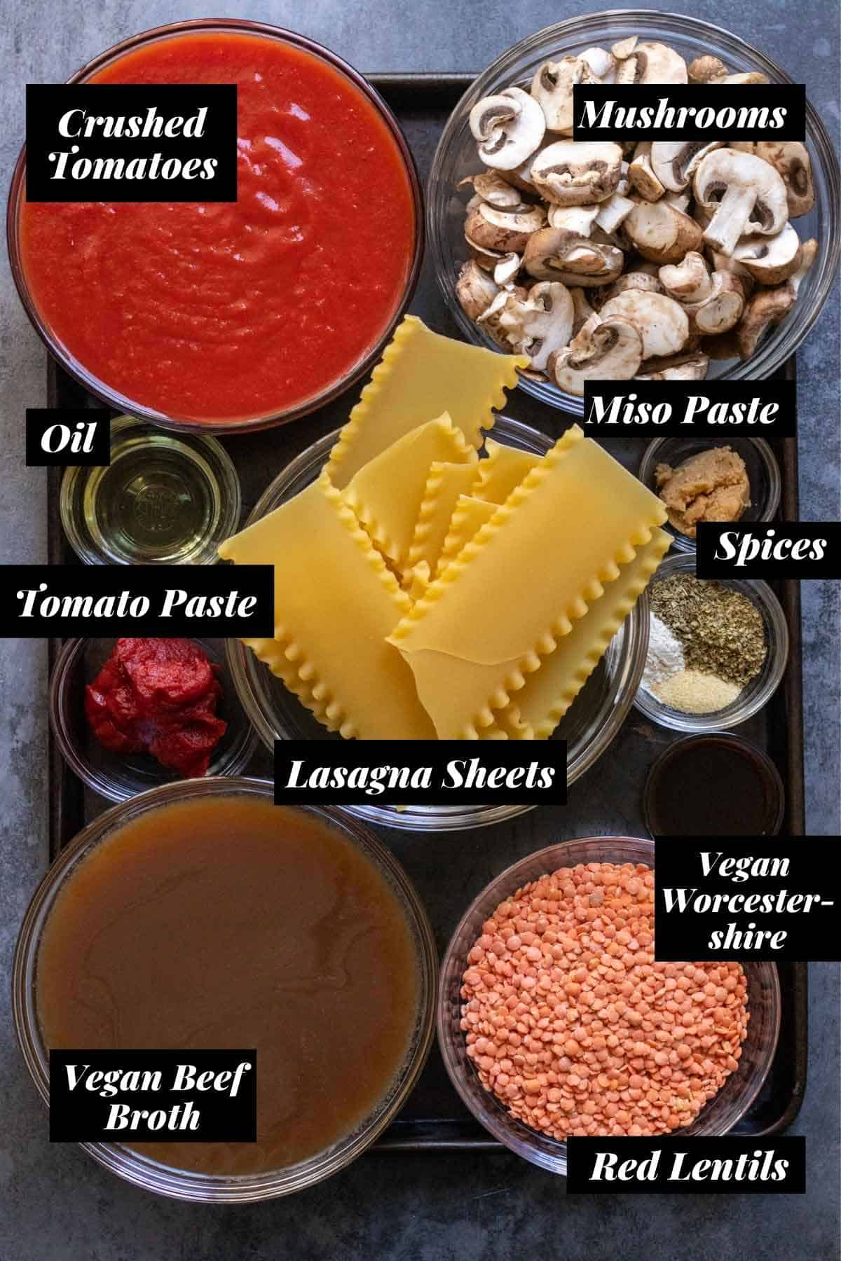 Ingredients needed for lasagna soup measured into individual bowls on cookie sheet with labels.