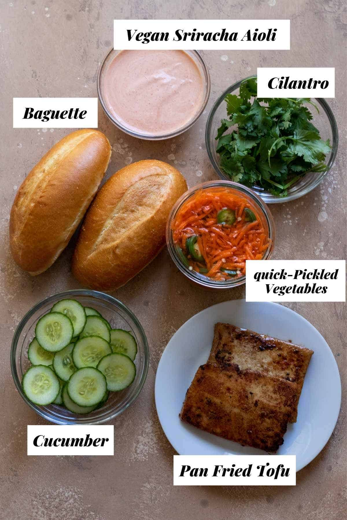 Ingredients needed to make a homemade tofu banh mi sandwich including baguette, cilantro, tofu, quick pickled vegetables, cucumber slices, and aioli.