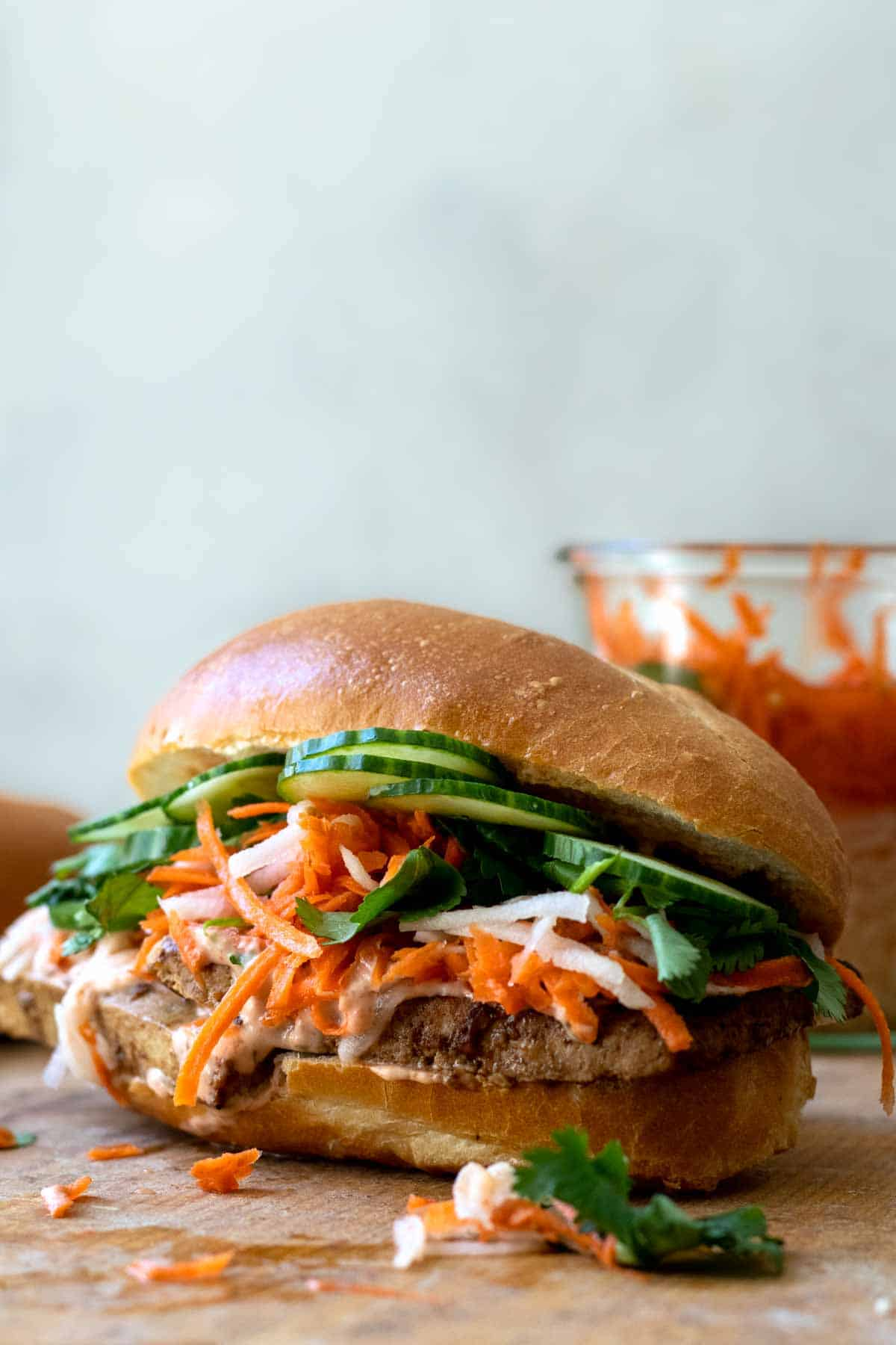 Tofu banh mi sandwich on wood cutting board with jar of quick pickled vegetables behind it.