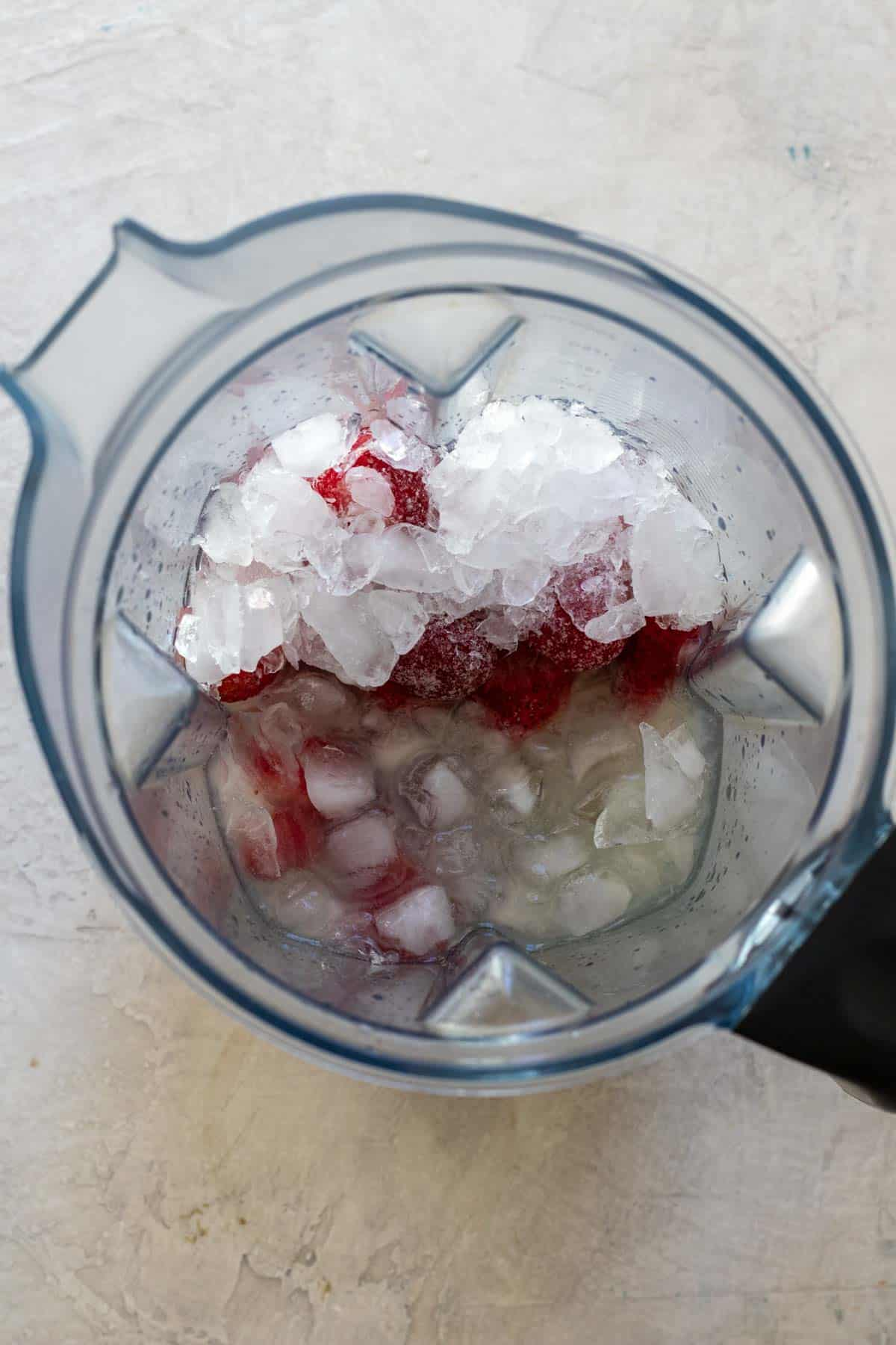 Frozen strawberries, crushed ice, tequila, lime juice and agave in blender before blending.