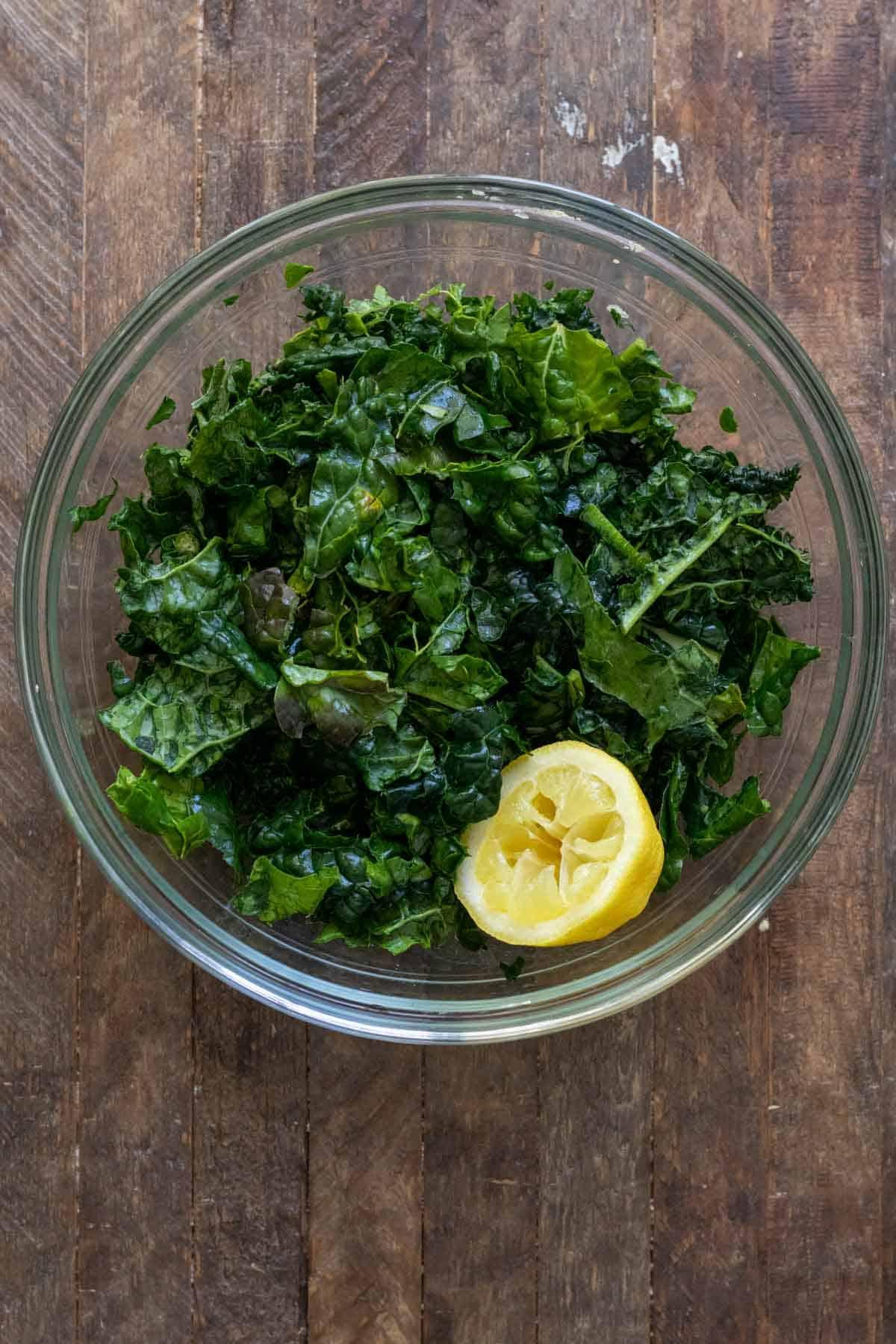 Kale in glass bowl massaged with lemon juice.